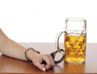 human handcuffed to alcohol drink