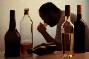 man drinking liquor at table