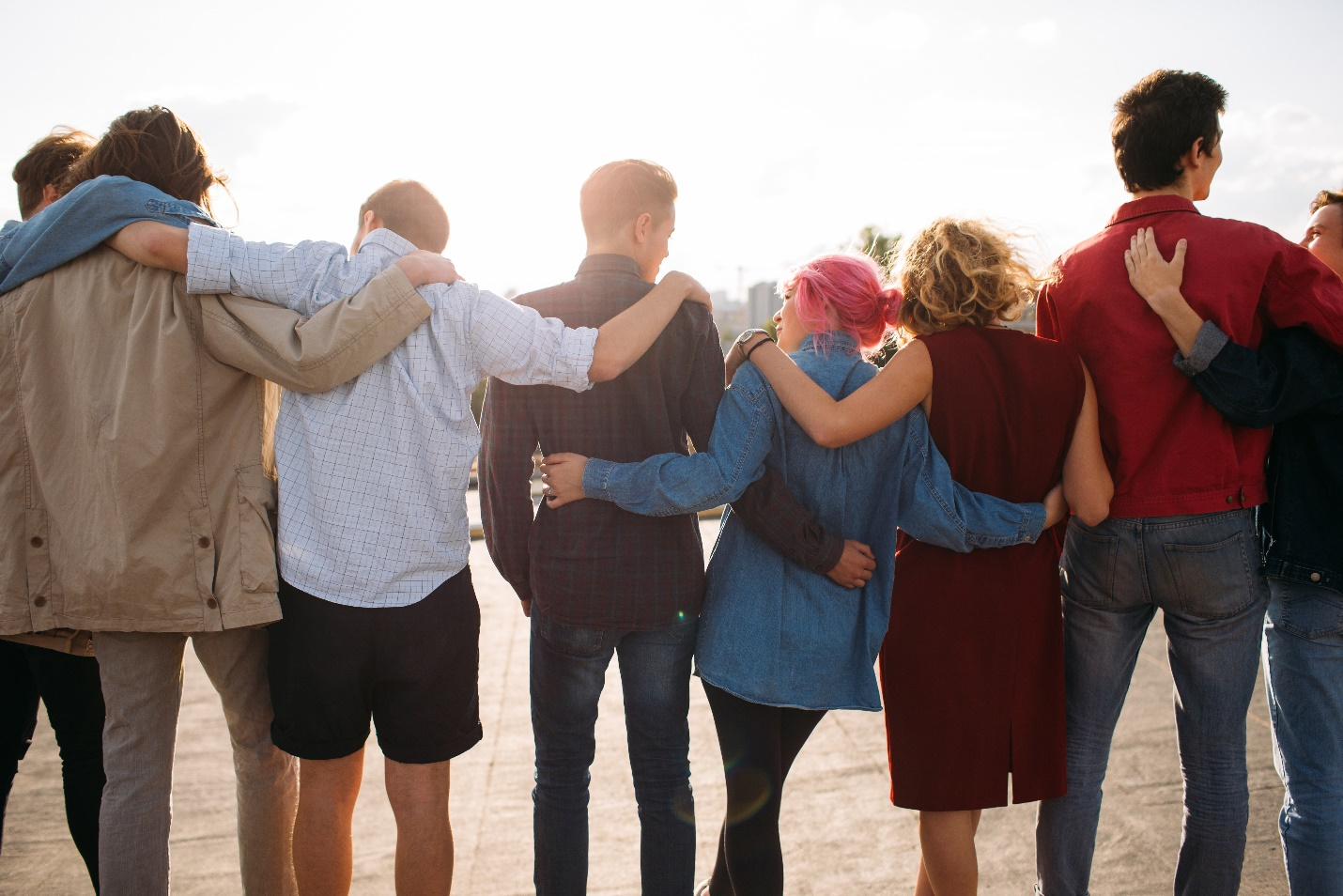 A group of teenagers who were former rehab patients side hugging one another.