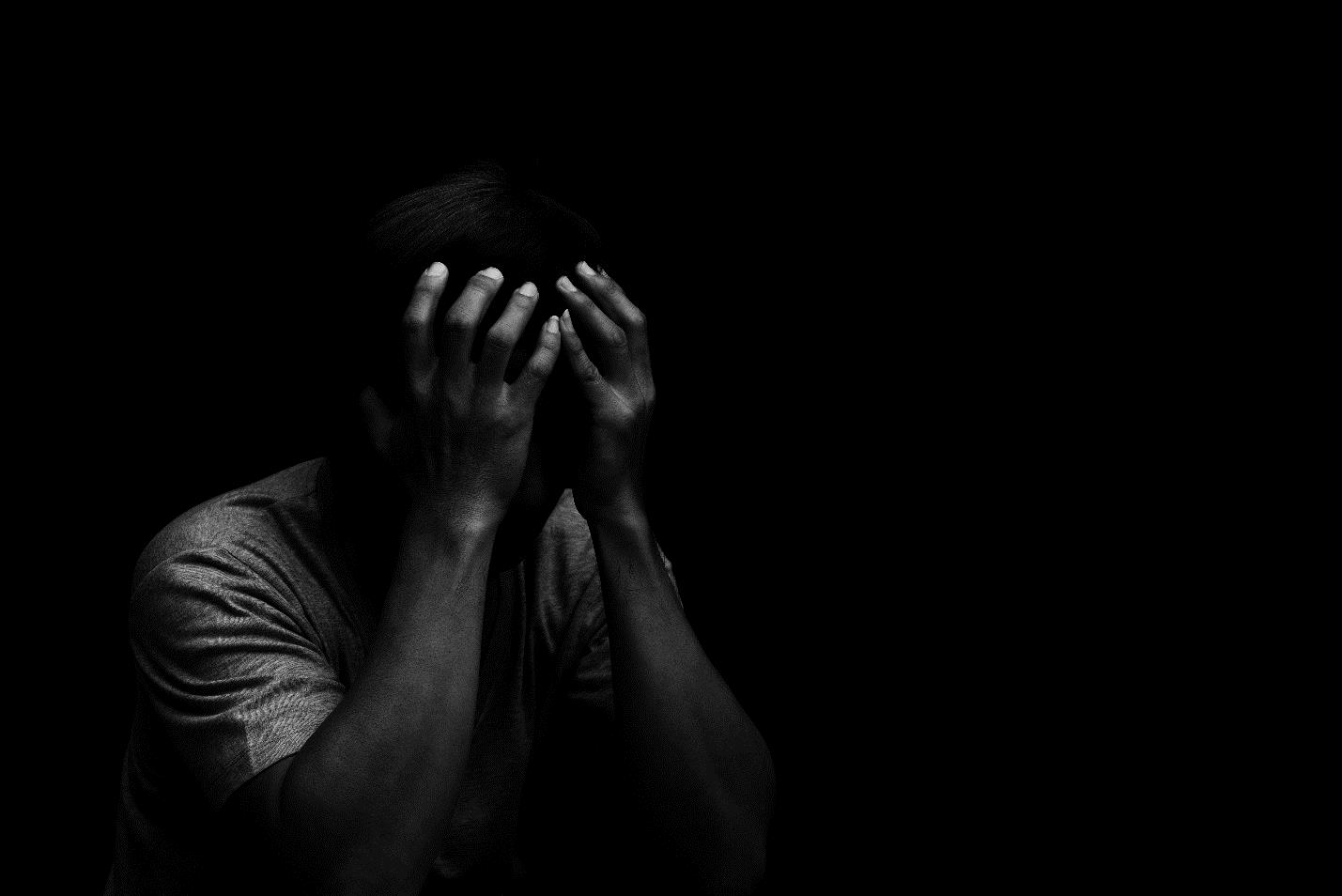 A person, depressed and exhausted, buried his face in his hands.