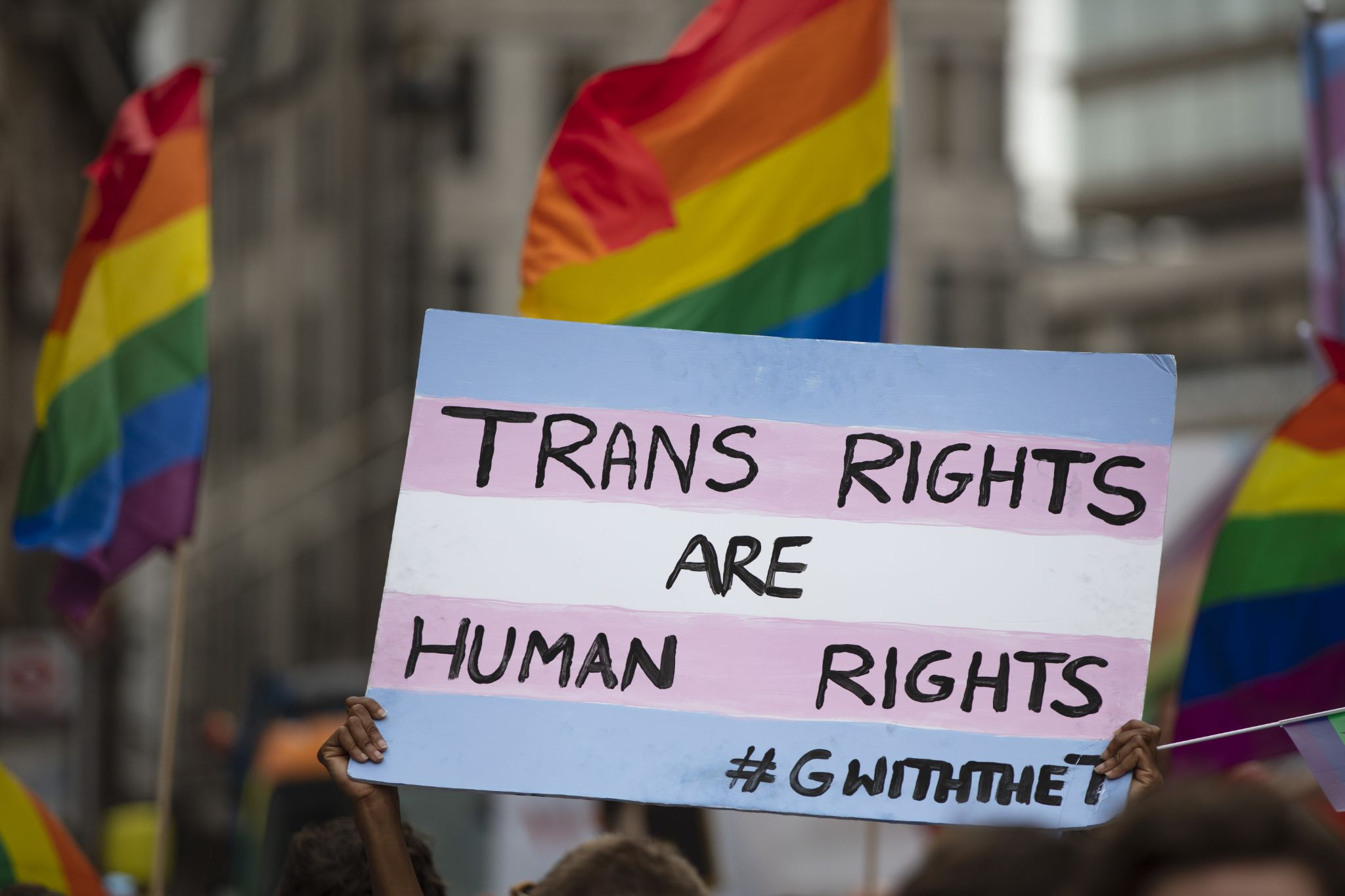 A person holding a pro transgender banner at a gay pride event