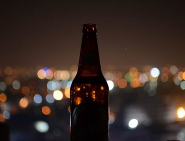 Beer Bottle On City Lights Background