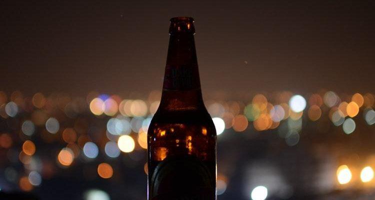 Beer Bottle On City Lights Background