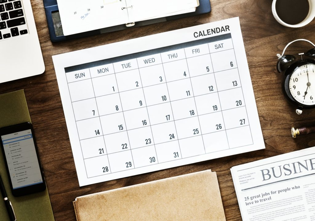 Calendar With Laptop On Office Desk