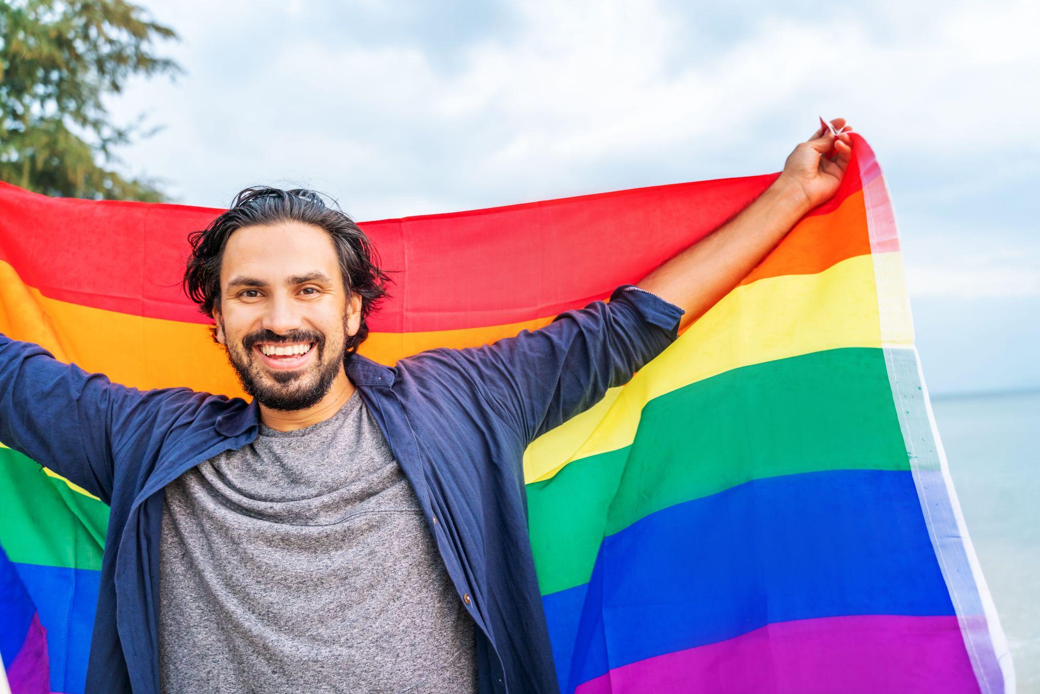 Young man holding a rainbow flag against the ocean sky