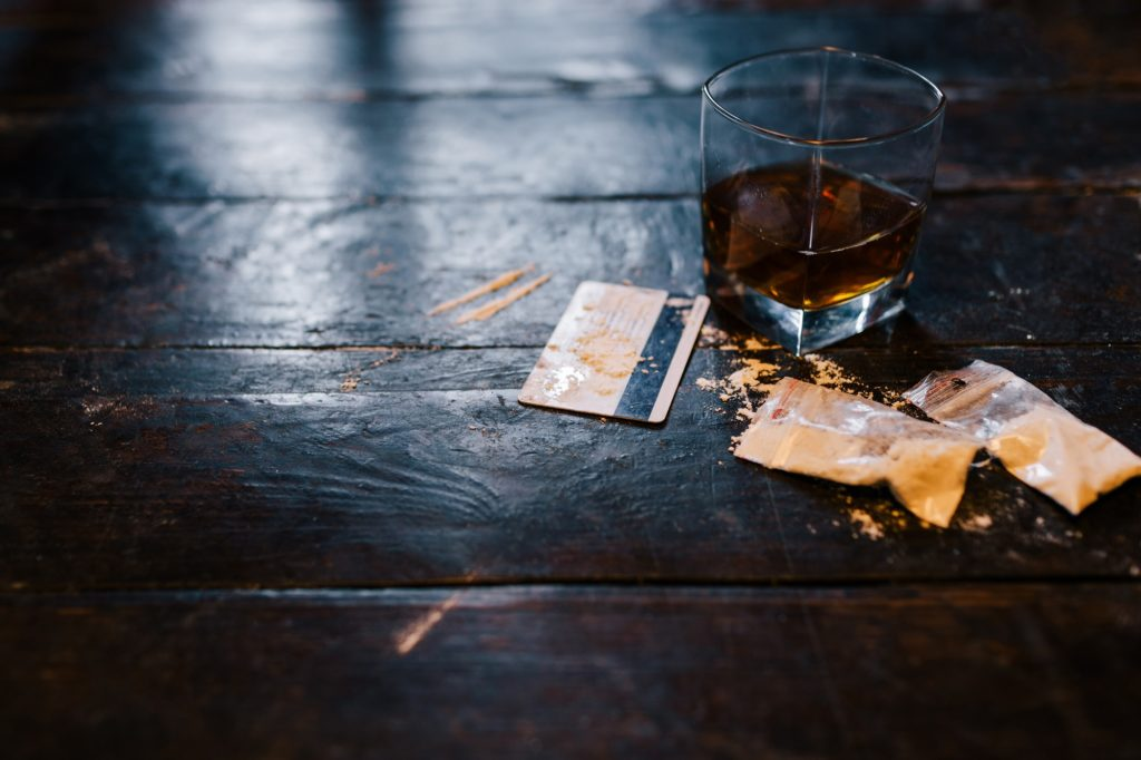 cocaine and alcohol drink with credit card on dark background