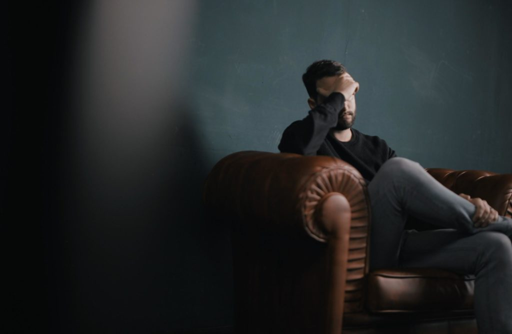 Depressed Man Sitting On Sofa