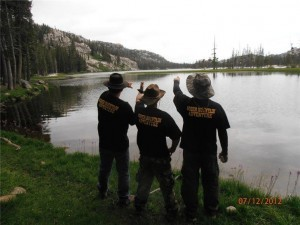 3 men discussing near the lake