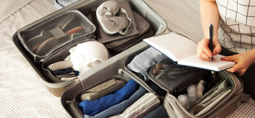 Female hands packing traveler case on bed