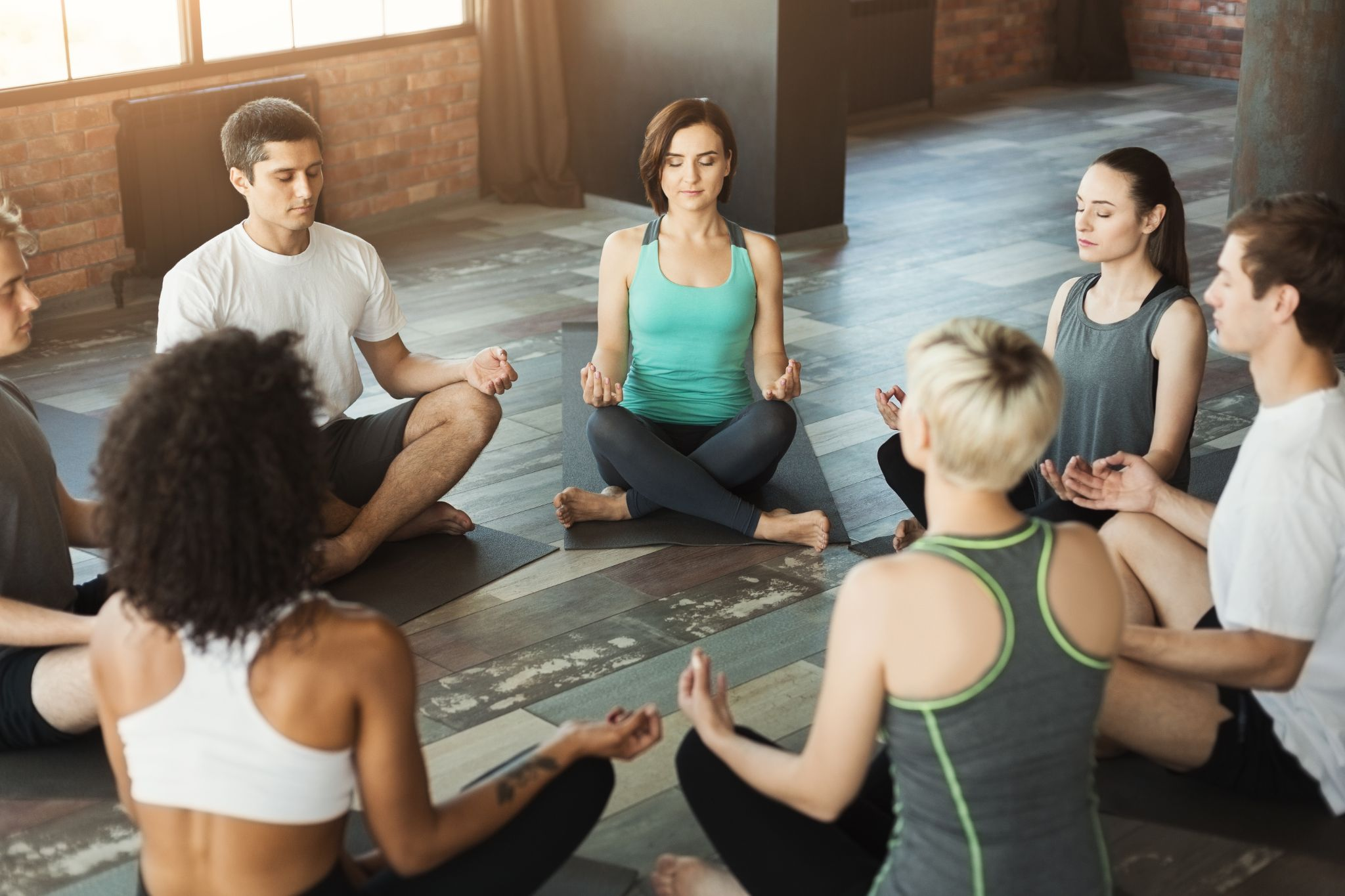 Group of young sporty people sitting in Sukhasana