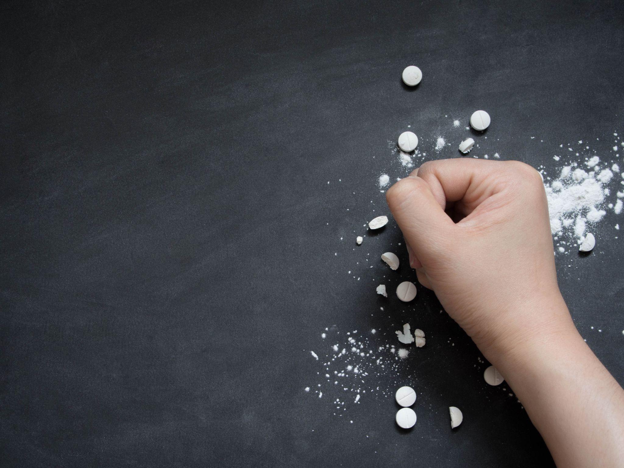 Human hands crushing white pills