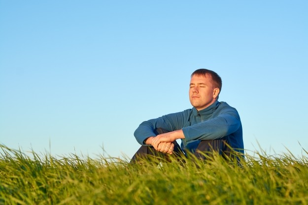 man meditating on grass