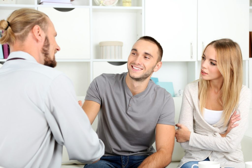 A recovering patient and his significant other talking with a counselor about IOP.