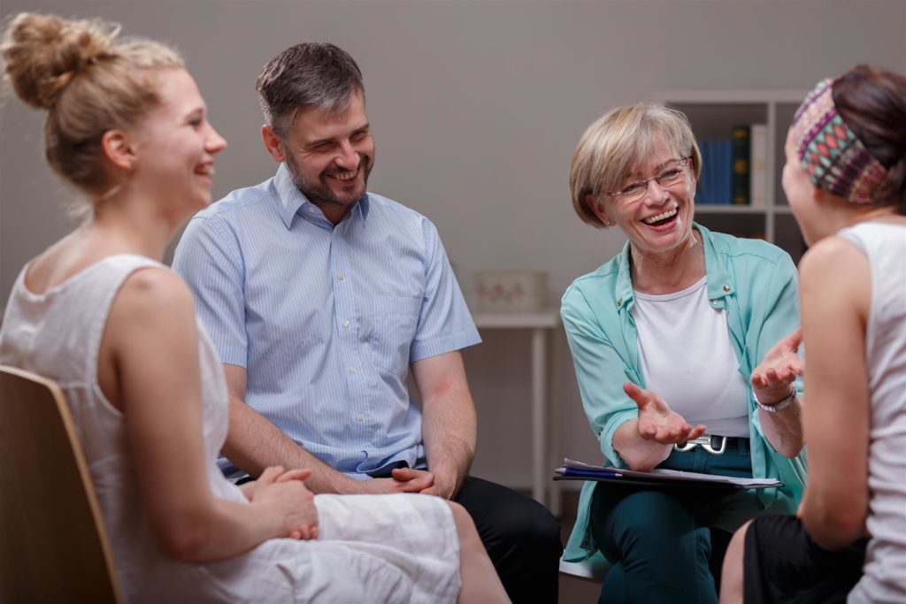 Recovering patients and a counselor chatting in an IOP's group therapy session.