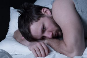 sad man laying down in bed