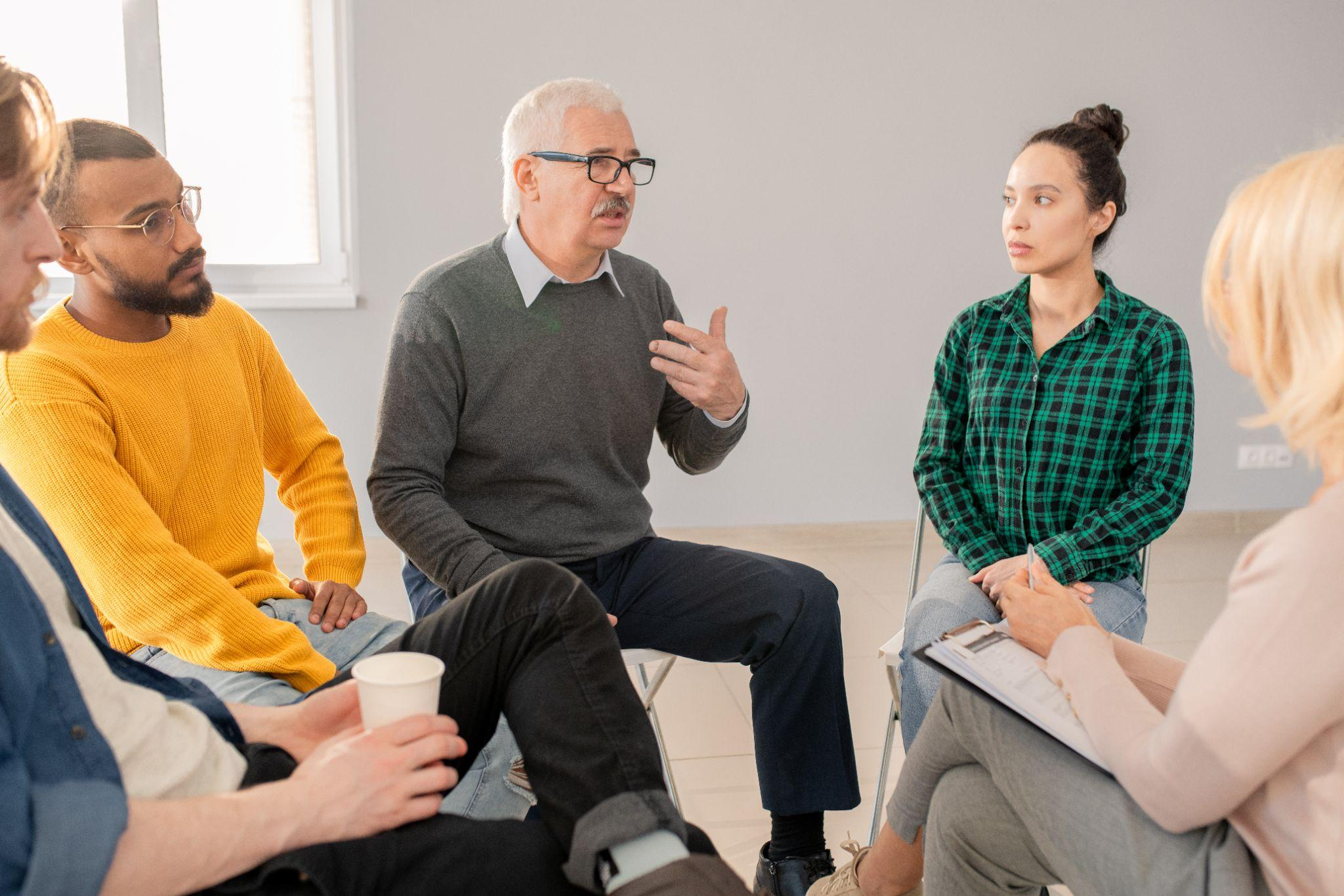 Senior man explaining his problem to groupmates at psychological session while thay listening to him