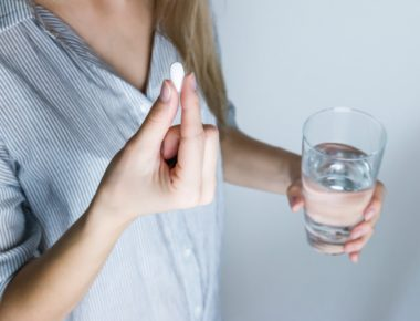 woman holding glass water and white medicine pill