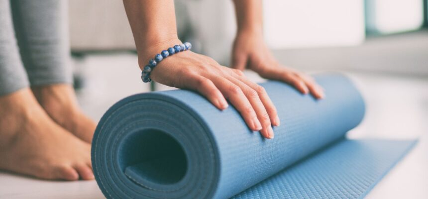 woman rolling exercise mat in living room for morning meditation yoga