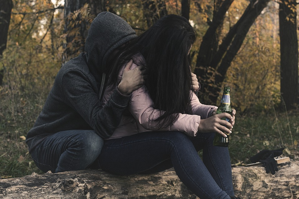 man hugging female holding beer
